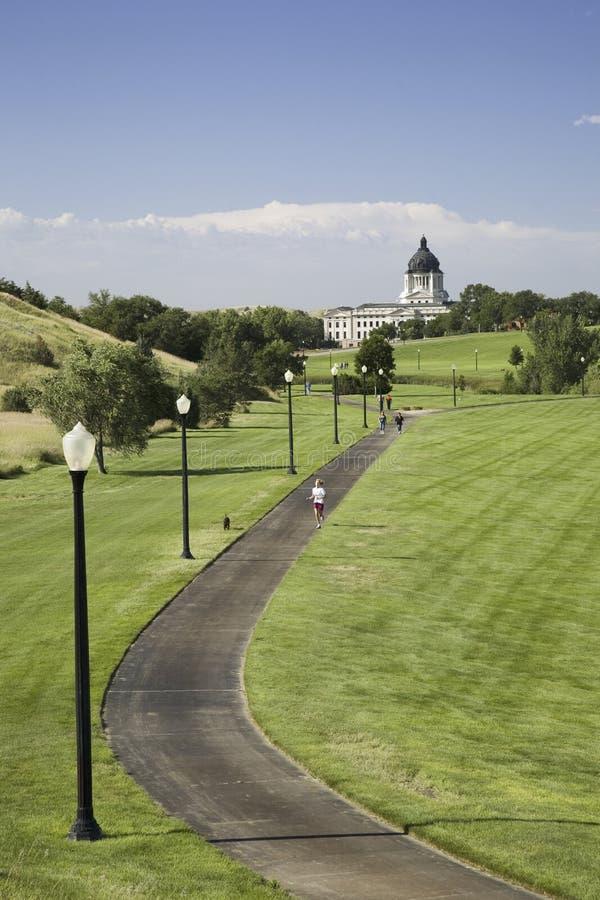 跑步的轨道在城市停放导致南达科他状态国会大厦 免版税库存照片