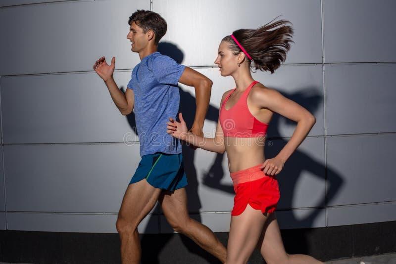 跑步肩并肩在都市街道的活跃年轻夫妇在他们的在健康和健身概念的每日锻炼期间 图库摄影