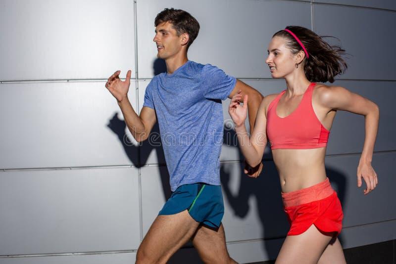 跑步肩并肩在都市街道的活跃年轻夫妇在他们的在健康和健身概念的每日锻炼期间 免版税图库摄影