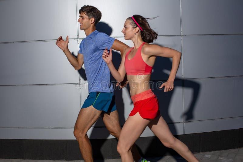 跑步肩并肩在都市街道的活跃年轻夫妇在他们的在健康和健身概念的每日锻炼期间 库存照片