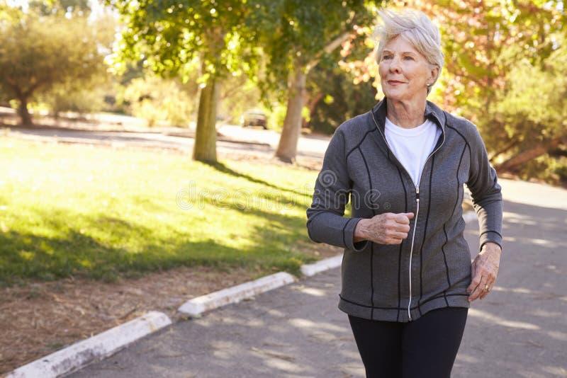 跑步通过公园的资深妇女正面图 库存图片