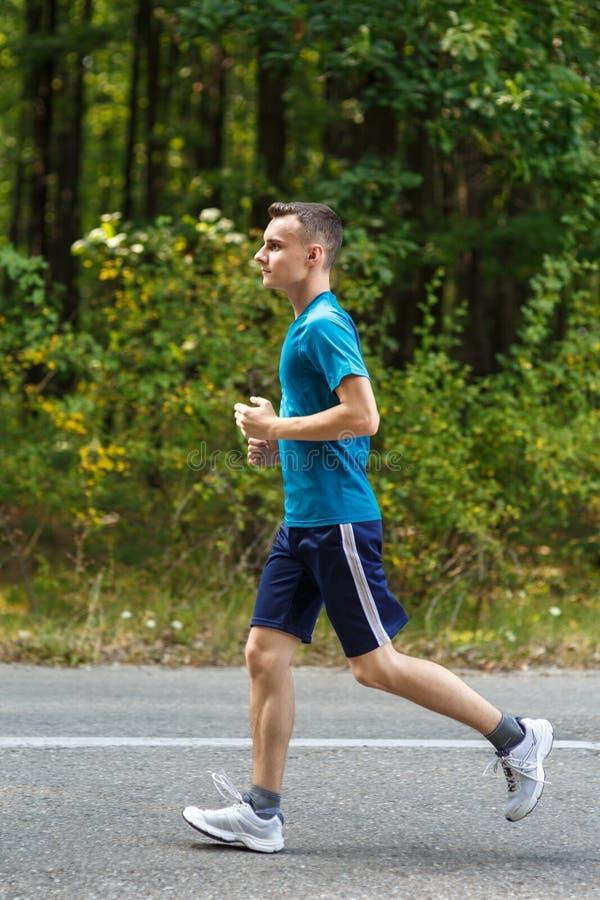 跑步通过森林的年轻男孩 库存图片
