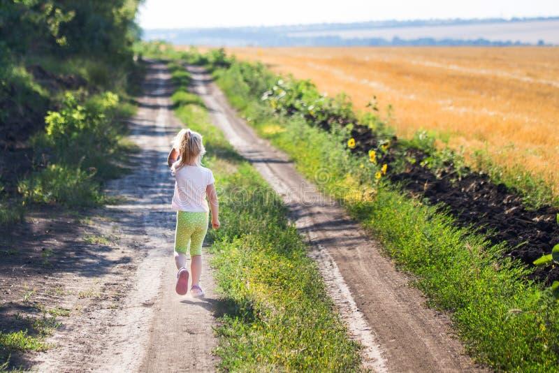 跑沿土农村路的小白肤金发的女孩 免版税库存图片