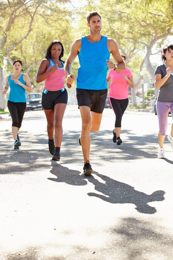 跑沿有个人教练员的街道的小组妇女 免版税库存照片