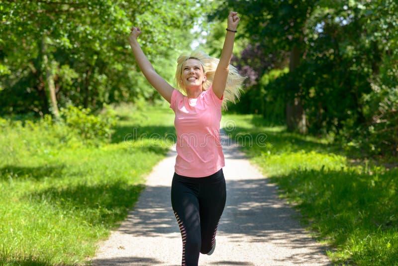 跑沿森林地轨道的快乐的妇女 免版税库存图片