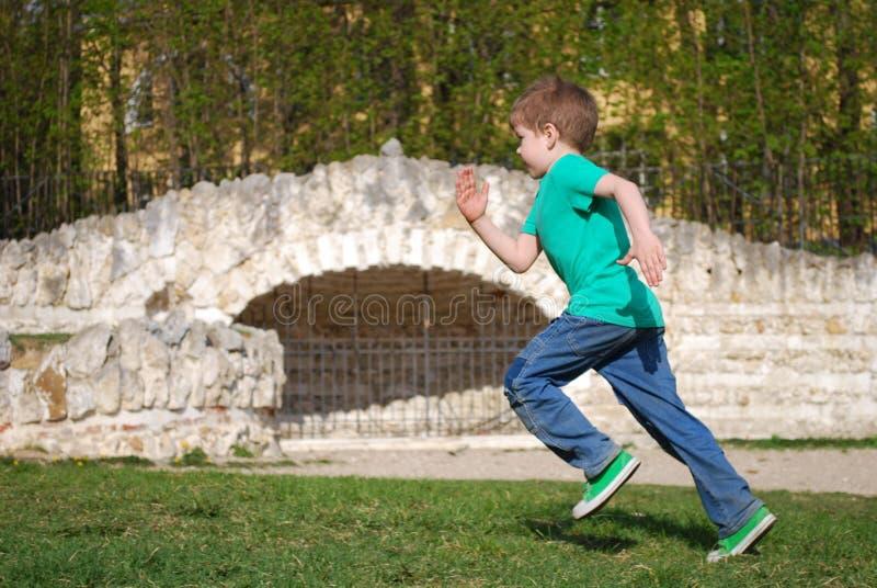跑沿森林道路的男孩 图库摄影