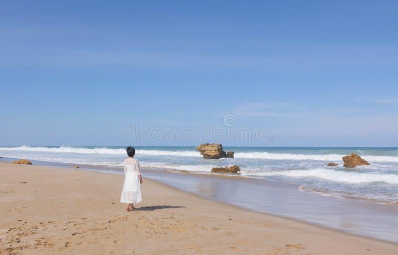 跑沿海滩的婚礼礼服的女孩 库存照片
