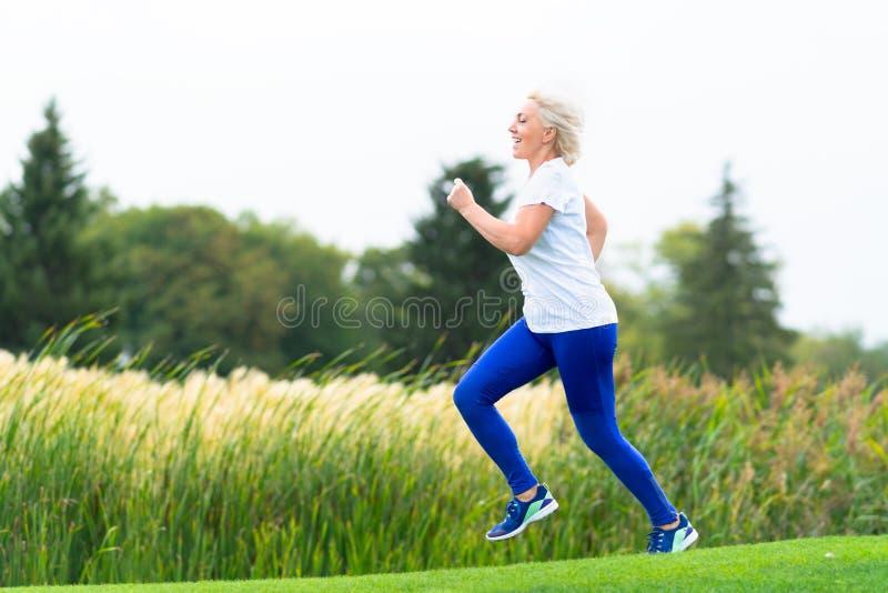 跑沿着芦苇的适合的运动成熟妇女 免版税库存照片