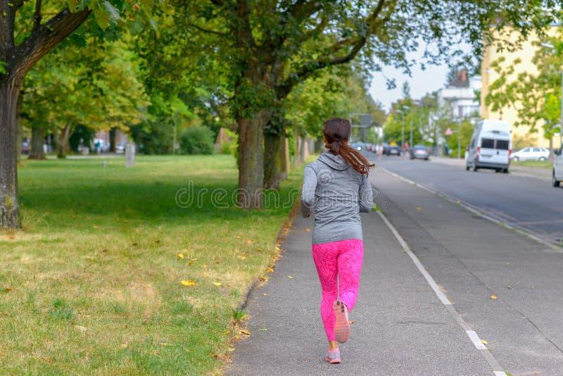 跑沿街道的成人慢跑者在公园旁边 免版税库存图片