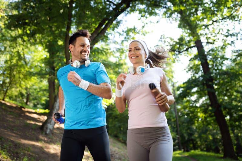 跑的年轻人户外 行使在公园的赛跑者的夫妇或朋友 免版税库存图片