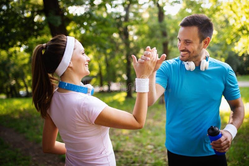 跑的年轻人户外 行使在公园的赛跑者的夫妇或朋友 免版税库存照片
