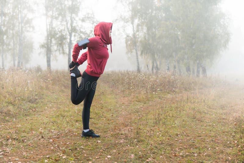 跑的舒展-做锻炼的妇女赛跑者在公园 免版税图库摄影