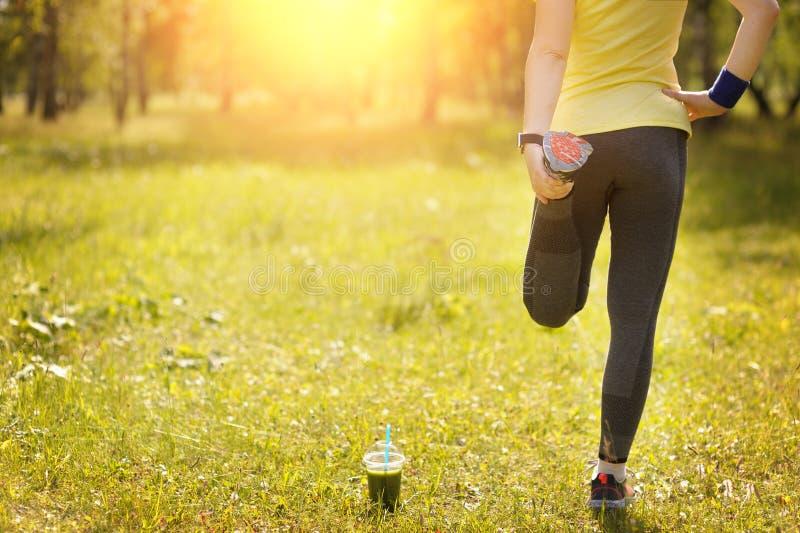 跑的舒展-妇女赛跑者佩带的smartwatch 免版税库存照片