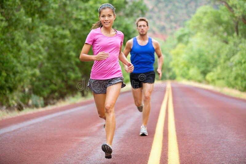 跑的运动员-炫耀跑步在夏天的夫妇 免版税库存照片