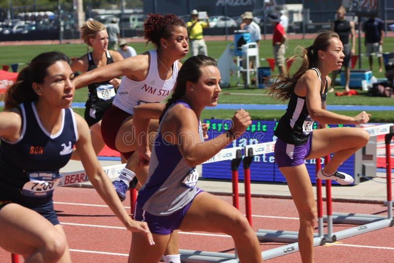 跑跨栏赛跑的学院妇女 免版税库存图片