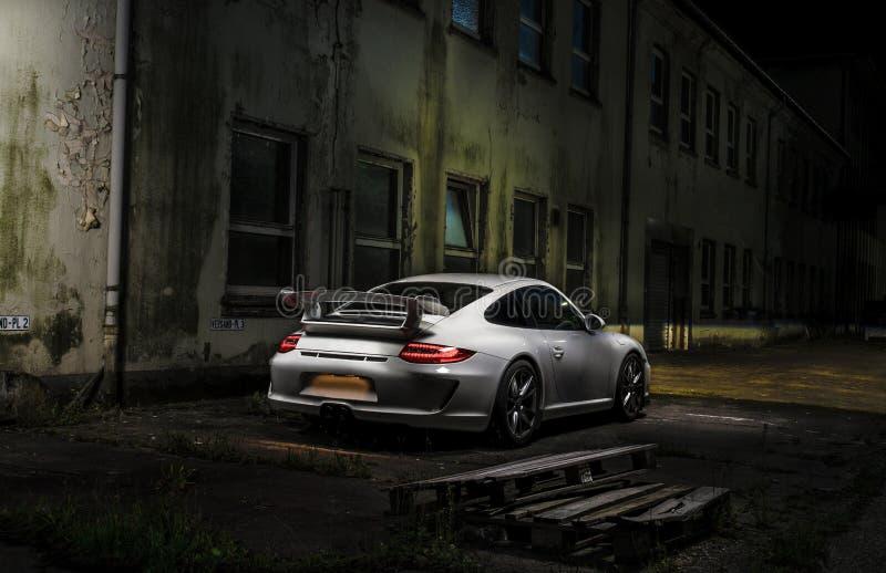 跑车在老工厂夜前面 免版税库存图片