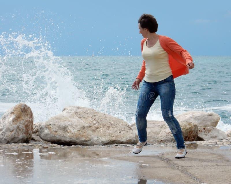 跑远离波浪的妇女 免版税库存图片