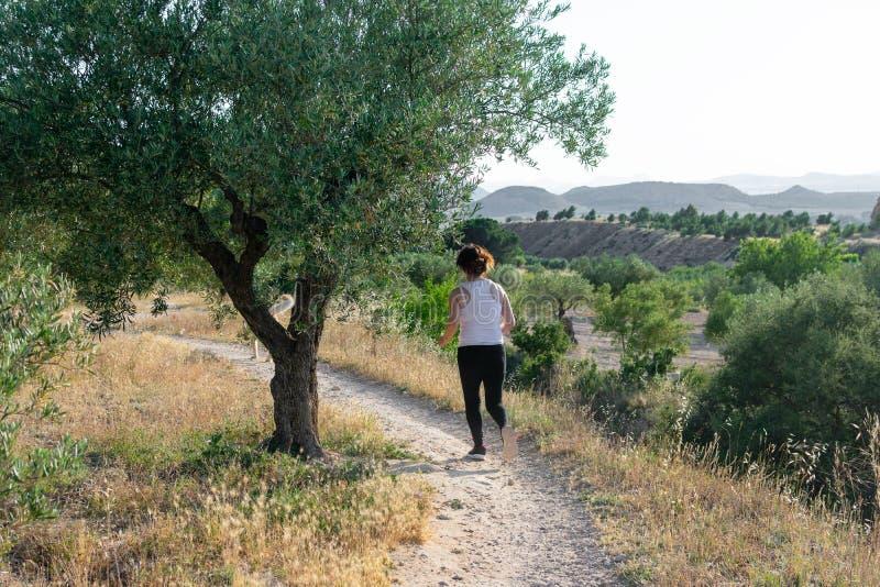 跑通过一个农村领域的适合的中年妇女 库存照片