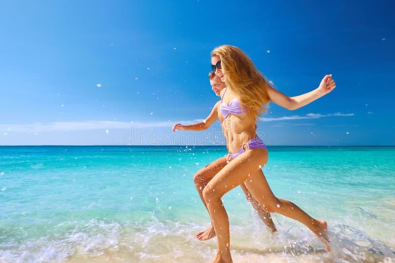 跑通过波浪的夫妇海滩假日 免版税图库摄影