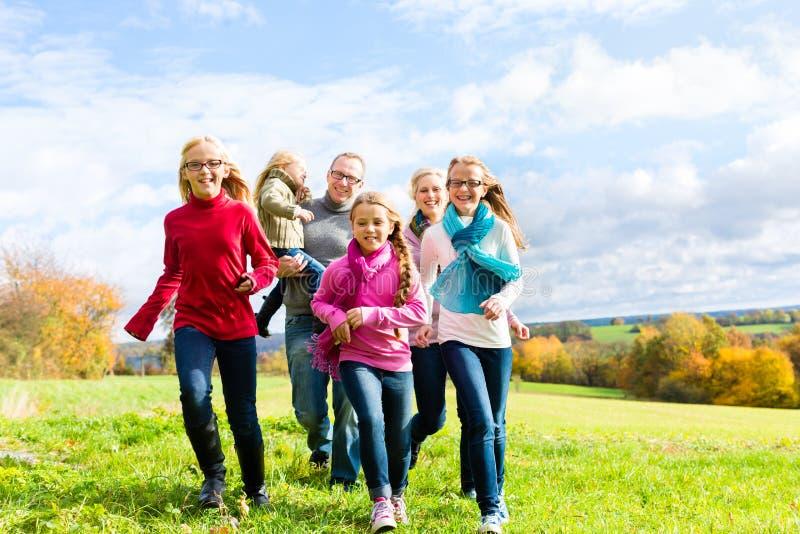 跑通过秋天的公园的家庭 免版税库存照片