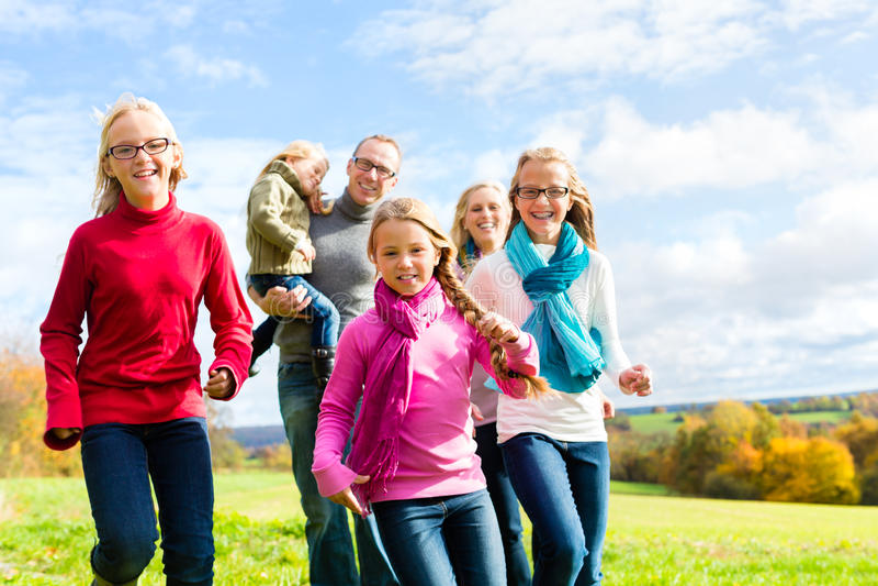 跑通过秋天的公园的家庭 库存照片