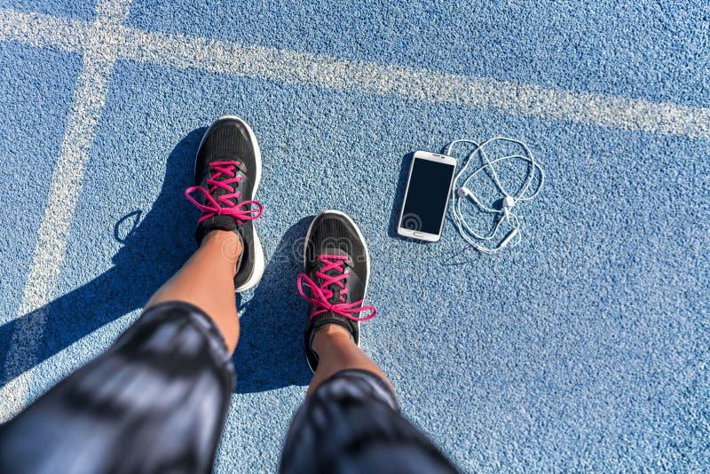 跑鞋女孩在跑的轨道车道的脚selfie 免版税库存图片