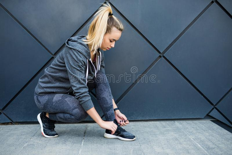 跑鞋-栓鞋带的妇女特写镜头 准备好母体育健身的赛跑者跑步户外 免版税图库摄影