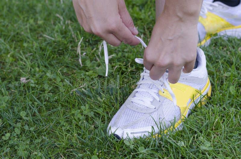 跑鞋-栓鞋带的妇女特写镜头 免版税库存图片