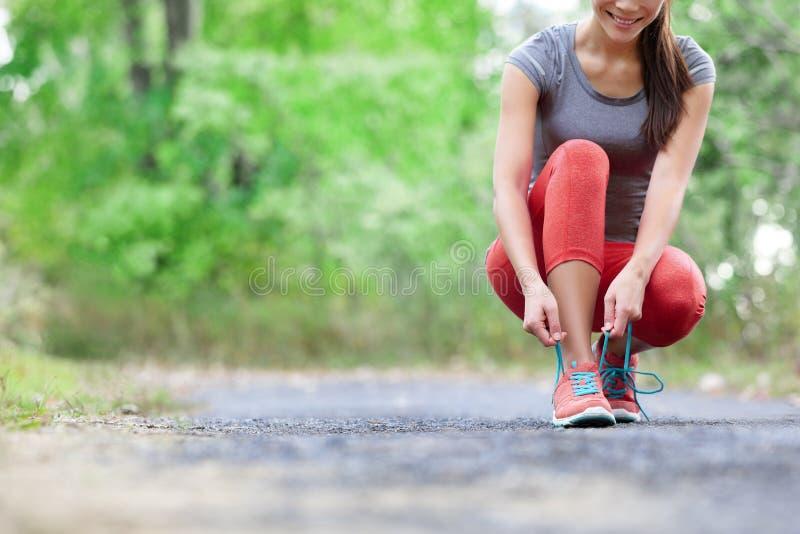 跑鞋-栓鞋带的妇女特写镜头 图库摄影