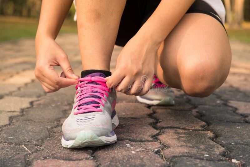 跑鞋-栓鞋带的妇女 准备好母体育健身的赛跑者特写镜头跑步户外在森林 库存图片