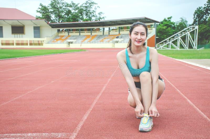 跑鞋-栓鞋带的妇女 准备好母体育健身的赛跑者跑步户外在轨道的车道 库存图片