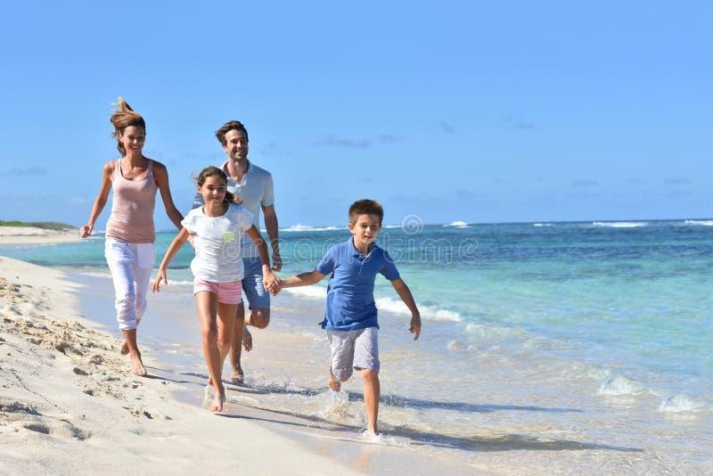 跑年轻的家庭享受暑假 免版税库存照片