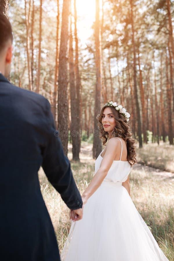 跟我学我的爱概念 可爱的少妇在握她的男朋友的手的白色婚礼礼服穿戴了 库存照片