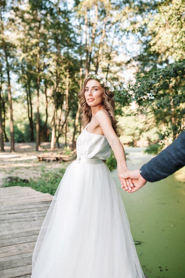跟我学我的爱概念 在她的男朋友和走的白色婚纱藏品手上打扮的可爱的年轻女人在 库存图片