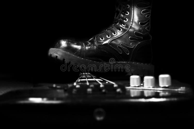 跨步在低音吉他的长统靴 硬岩和重金属 图库摄影