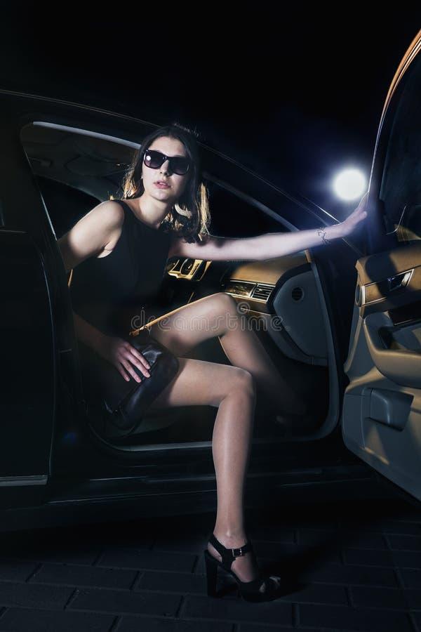 跨步在太阳镜的汽车和晚礼服外面的年轻端庄的妇女在一个隆重的事件 免版税库存图片
