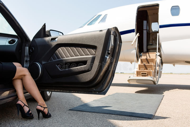 跨步在汽车外面的富裕的妇女在终端 免版税库存照片