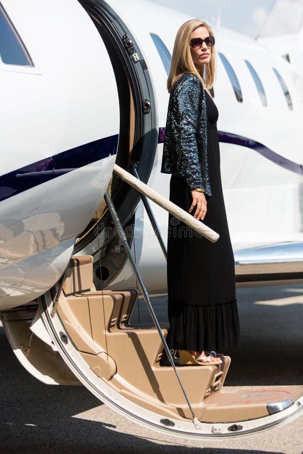 跨步在私人飞机外面的富裕的妇女 库存照片