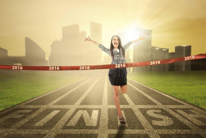 跨过终点线的女性优胜者 图库摄影