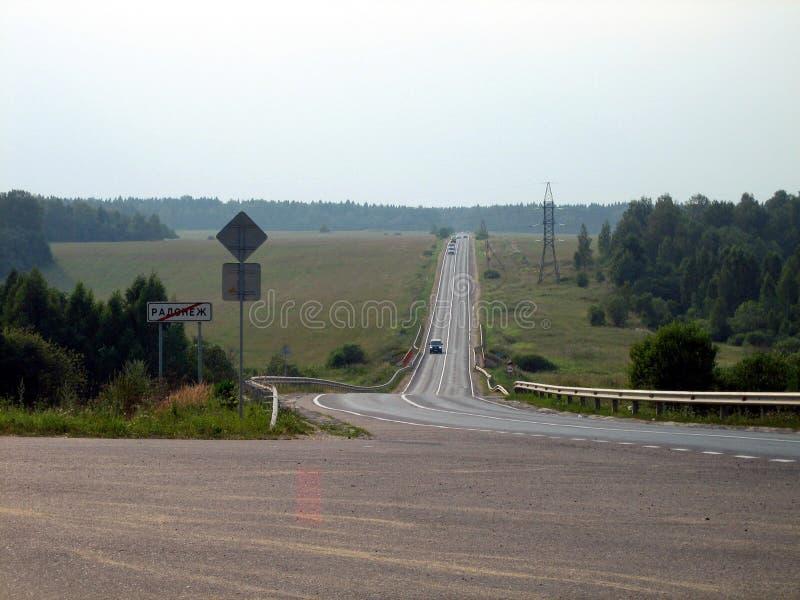 路一条灰色丝带在领域和森林之间的在一阴天 免版税图库摄影