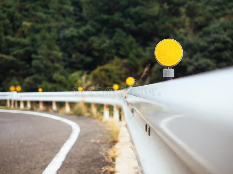 路与黄色反射标志小心的曲线障碍 库存照片