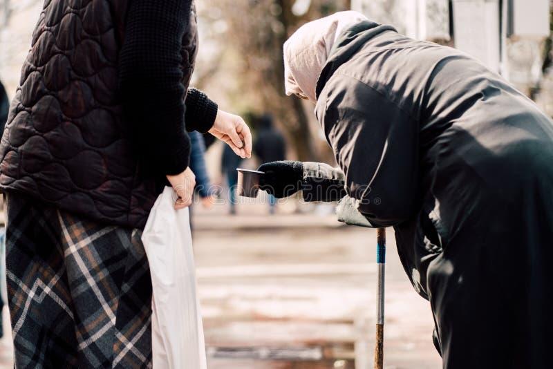路人givining的施舍照片老饥饿的无家可归的女性叫化子的在街道上 图库摄影