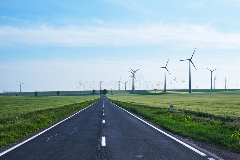 路今后与风轮机匹配在它的边和到距离里,在天空蔚蓝 能承受的能量解答的概念 库存照片