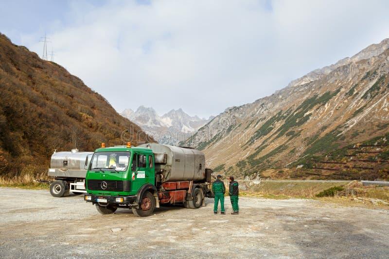 路修理 站立在他们的卡车前面的路工作者 圣安东上午Arlberg,蒂罗尔,奥地利的自治市 免版税库存图片