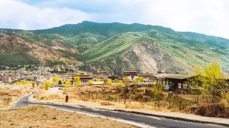 路和村庄有高山和巨大的云彩的在廷布上 免版税库存照片