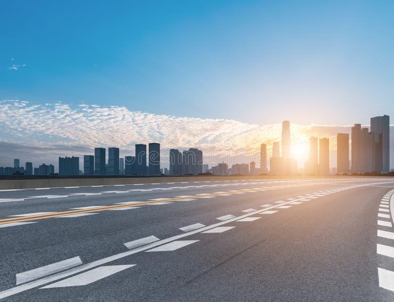 路和现代城市地平线在日出 库存照片