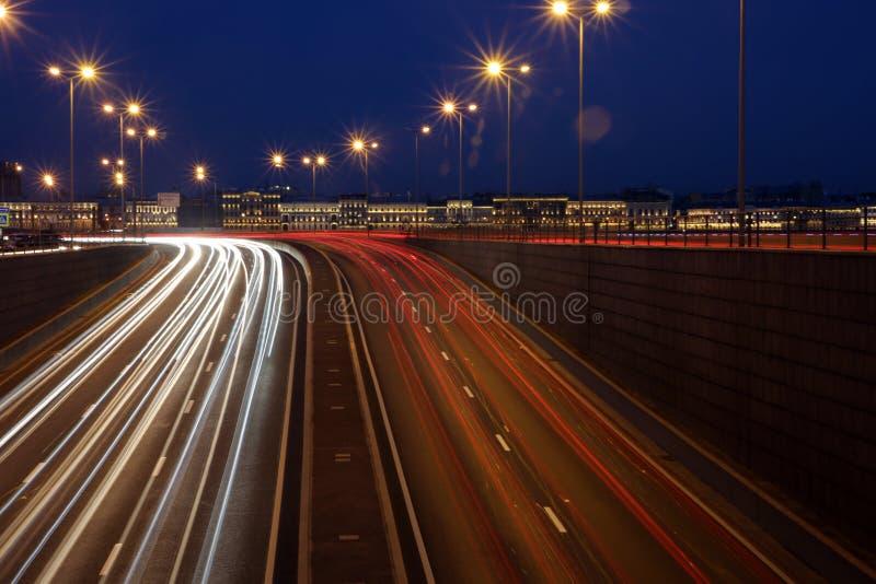 路在圣彼德堡、移动的他们的光亮车灯汽车和足迹的晚上  库存图片