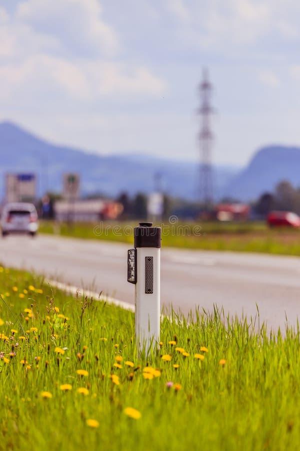 路在夏天:反射器岗位、汽车、花和绿草 免版税库存图片