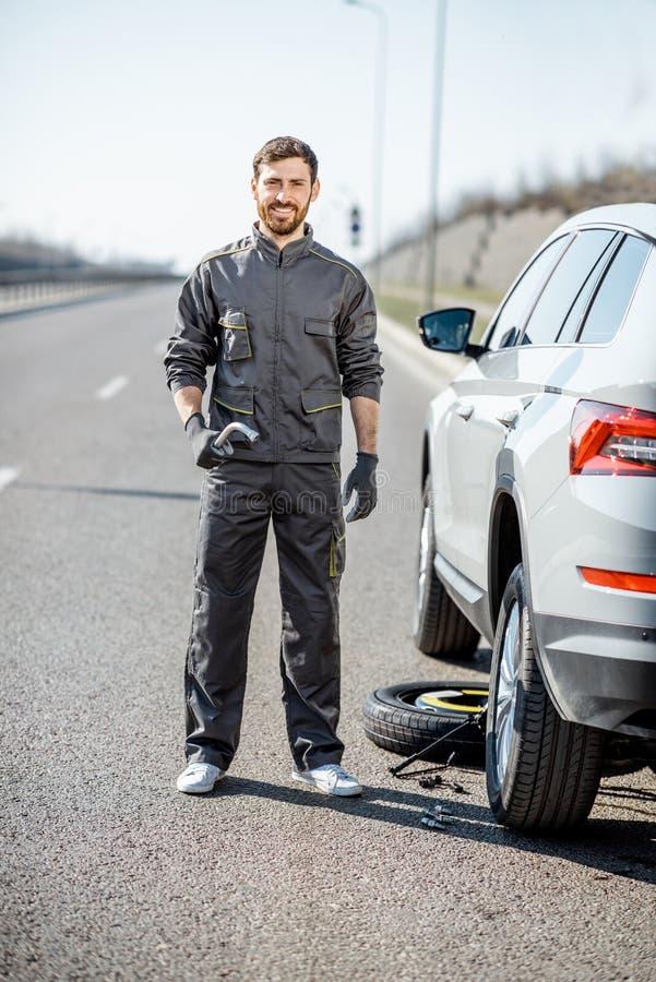 路在汽车附近的协助工作者在高速公路 免版税库存图片
