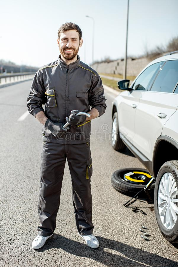 路在汽车附近的协助工作者在高速公路 免版税库存照片